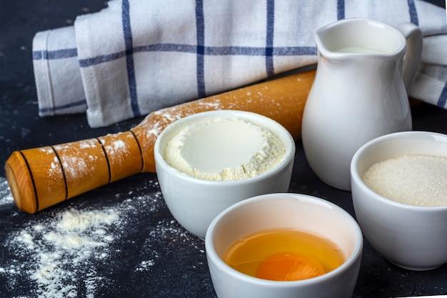 Выпечка фон. ингредиенты и посуда для приготовления торта на темном столе. концепция питания.