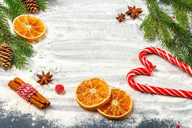 Рождественская плоская композиция. рамка еловые ветки, шишки, анис, корица и сушеные апельсины на фоне муки. рождество, зимние каникулы, концепция нового года. скопируйте место для текста.