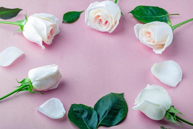 Круглая рамка из белых роз и зеленых листьев