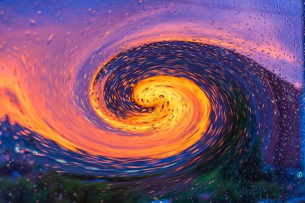 Яркий огненный закат через капли дождя на окне с боке огни. аннотация