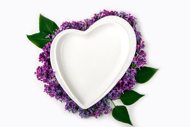 Пустая тарелка в форме сердца, украшенная сиреневыми цветами