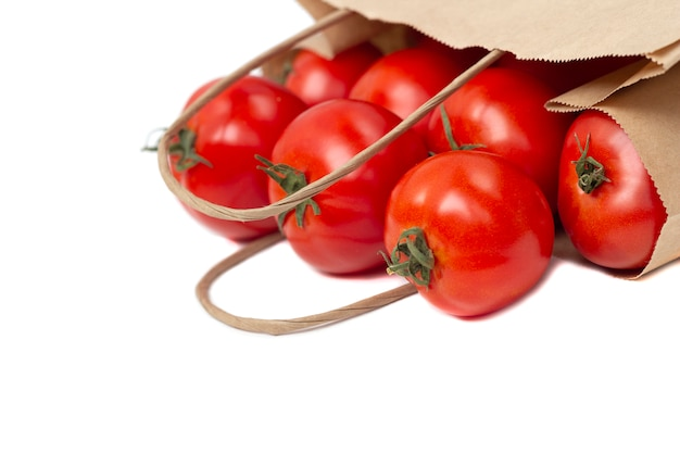 分離されたエコバッグで新鮮な健康トマト。オーガニックおよびベジタリアンフードのショッピング。廃棄物ゼロ、環境に優しい、またはプラスチックを使用しない寿命