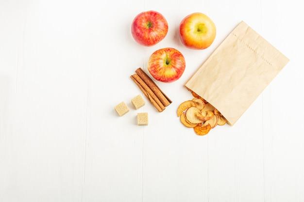 紙エコパックと新鮮なリンゴ、シナモンスティック、白の砂糖の有機自家製ドライフルーツチップ