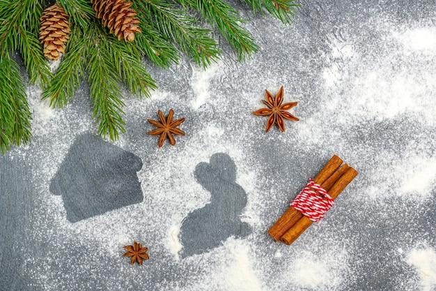 クリスマスの組成物。クリスマスツリーの枝、コーン、スターアニス、シナモンの中でクッキーの小麦粉のシルエット。