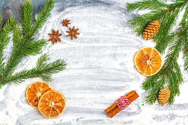 クリスマスフラットレイアウト構成。モミの枝、コーン、スターアニス、シナモン、小麦粉の背景に乾燥オレンジのフレーム。クリスマス、冬休み、新年のコンセプト。コピースペース。