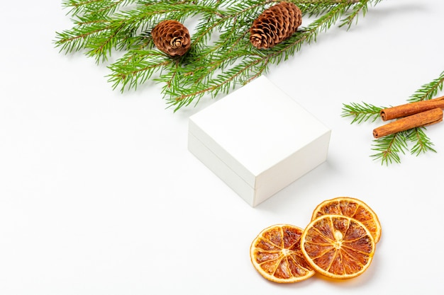 ドライオレンジフルーツ、シナモンスティック、コーン、スプルースクリスマスツリーの小枝と白のモックアップギフトボックス