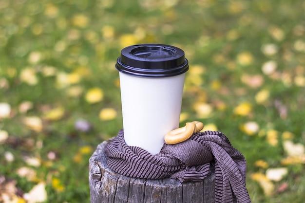 Осенняя композиция. чашка кофе на пне в парке. кофе идти среди осенних листьев.