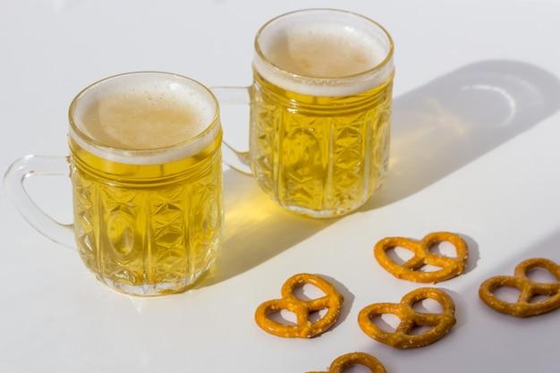 オクトーバーフェストのコンセプト。塩プリッツェル、ブレッツェルのスナックとビールジョッキ