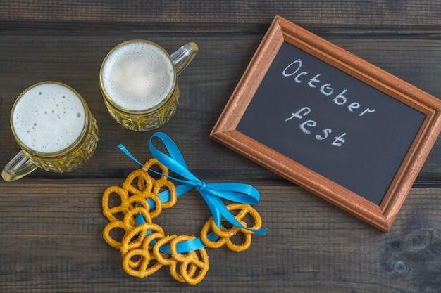 オクトーバーフェストのコンセプト。暗い木製のテーブルに塩オムレツ、ブレッツェル、「オクトーバーフェスト」という言葉が書かれたボードのスナックを添えたビールジョッキ。