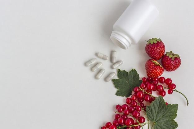 薬瓶からの新鮮な果実のカプセルとしてのビタミンサプリメント。