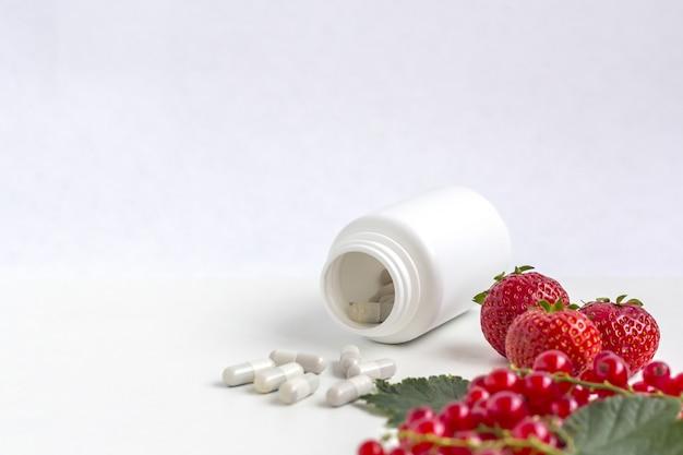 薬の白い錠剤瓶からの新鮮な果実とカプセルとしてビタミンサプリメント。