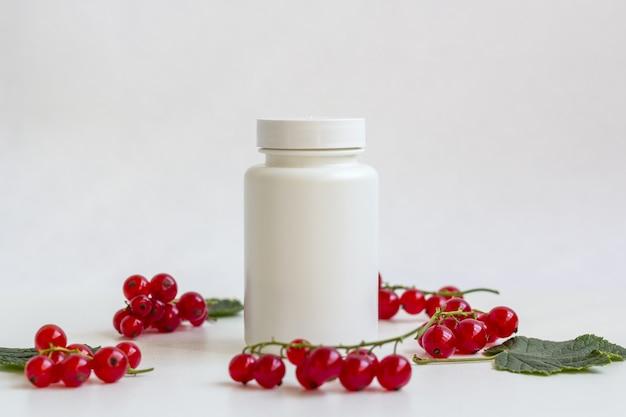 果実の中の錠剤またはビタミン栄養補助食品の白い薬瓶