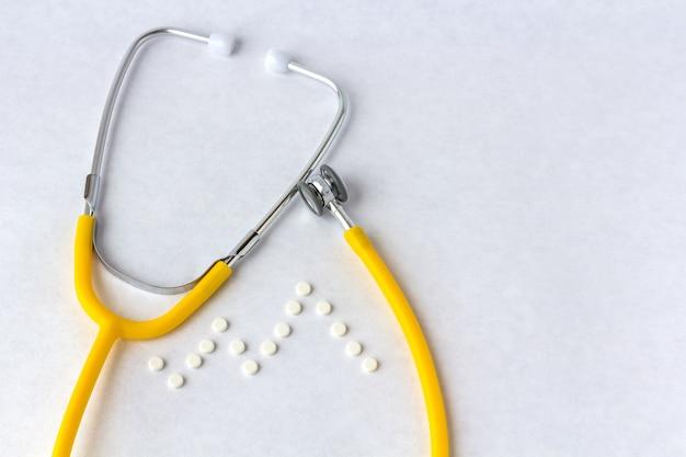 Медицинский стетоскоп с таблетками в виде кардиограммы