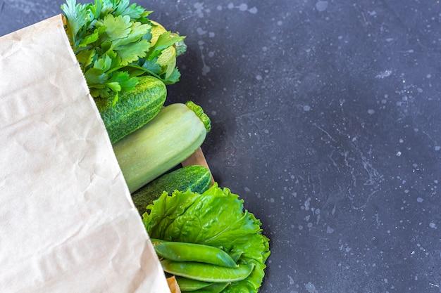 Бумажный пакет различных здоровых зеленых овощей на темной таблице. концепция правильного питания и здорового питания. органическая и вегетарианская еда. вид сверху, плоская планировка, копирование пространства для текста.