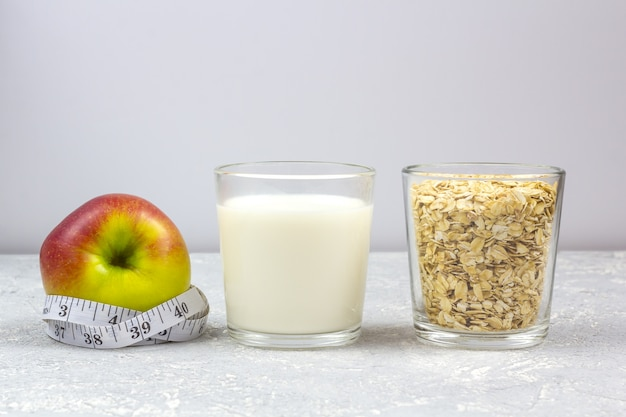 牛乳とオート麦フレーク(オート麦)のガラス。測定テープ付きアップル。