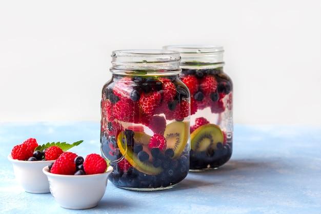 ラズベリー、ブルーベリー、キウイとメイソンジャーマグカップで新鮮なクールなデトックスドリンク。ミントとガラスのレモネード。適切な栄養と健康的な食事の概念。フィットネスダイエット