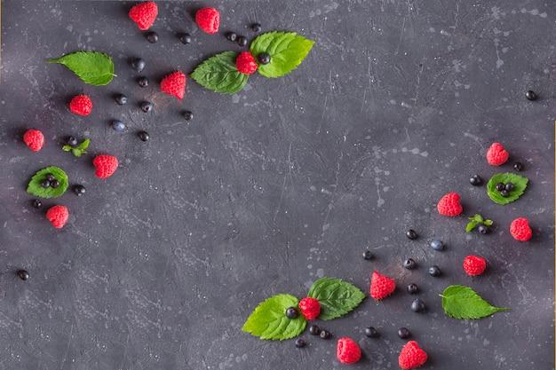 新鮮なジューシーなラズベリーとミントとブルーベリーは、暗い背景に残します。黒の夏の果実。健康、ベジタリアン、食事、ダイエット。