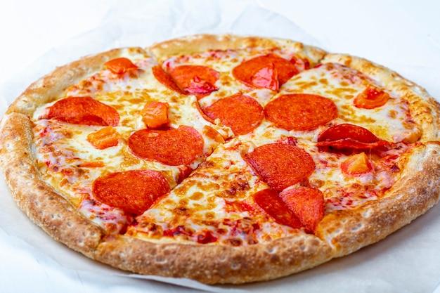 白い背景にサラミ、トマト、チーズの新鮮な準備のおいしいペパロニピザをクローズアップ。イタリアの伝統的なランチまたはディナー。