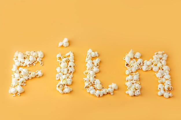 「フィルム」という言葉は、オレンジ色の背景に新鮮なポップコーンからレイアウトされています。シネマスナックコンセプト。映画やエンターテイメントを見るための食べ物。トップビュー、フラットレイアウト。