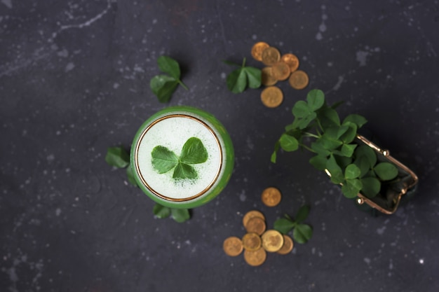 緑の財布からの新鮮なクローバーの葉と金貨は暗い背景に散在しています。聖パトリックの日の概念、フラットレイアウト