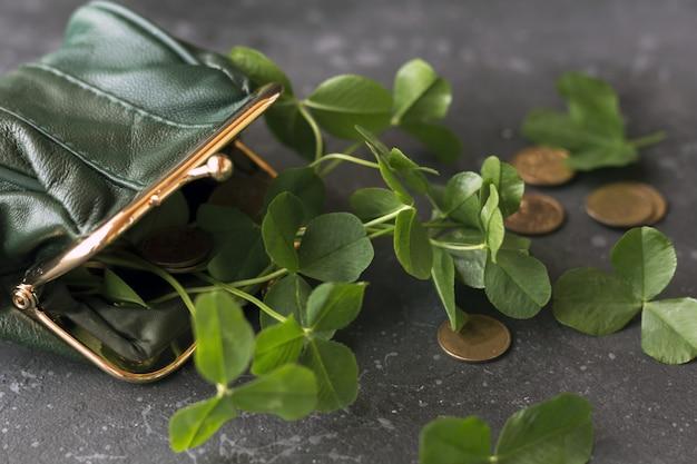 緑の財布からの新鮮なクローバーの葉と金貨は暗い背景に散在しています。聖パトリックの日のコンセプト。