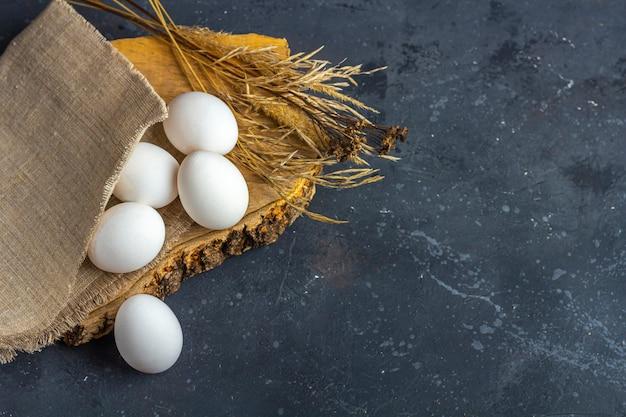 イースターフラットは暗い背景に卵細胞の新鮮な白い卵の素朴な組成物を置きます。廃棄物ゼロ、環境に優しい自然素材。農業と健康的な食事のコンセプト。