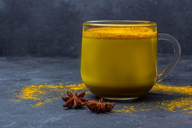 伝統的なインドの飲み物ターメリックミルクは、暗い背景にシナモン、アニススター、ウコンとガラスのマグカップで黄金のミルクです。減量、健康的なオーガニック飲料