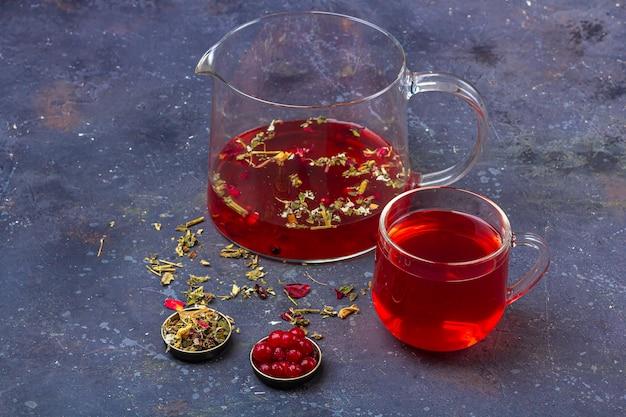 乾燥茶葉、花びら、暗い背景上のクランベリーの中でガラスカップとティーポットの赤茶(ルイボス、ハイビスカス、カルカデ)。風邪やインフルエンザのためのハーブ、ビタミン、デトックスティー