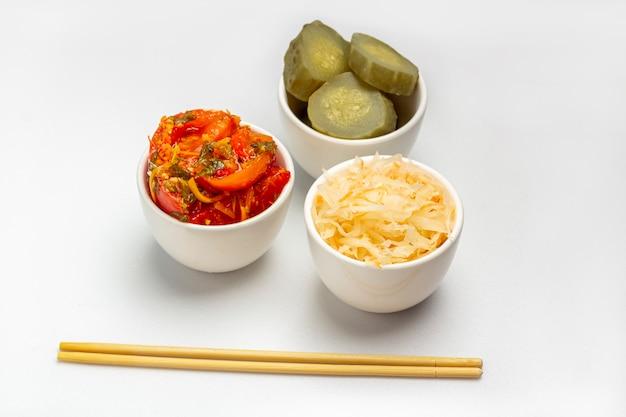 発酵野菜、ザワークラウト、塩味の保存漬物キュウリとトマトの白い背景の上。健康的な食事。有機農場のベジタリアン料理