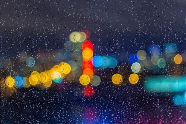 ボケライトと夜の窓に雨滴。抽象的な背景、ガラスの水滴、夜の街の明かり。