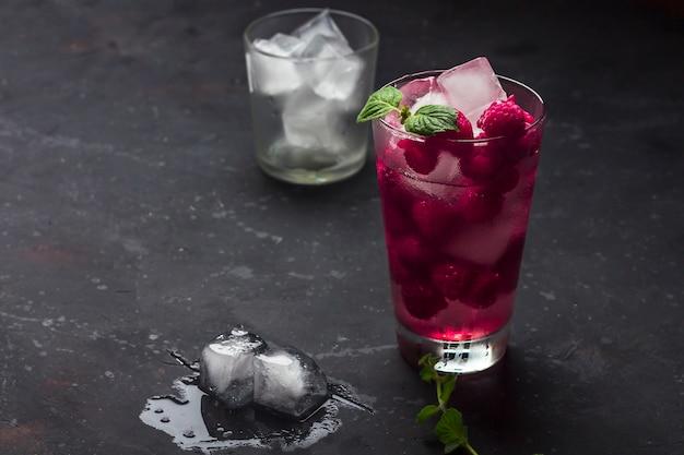 暗い背景にリキュール、ウォッカ、氷、ミントとラズベリーのアルコールカクテル。ラズベリーモヒート。さわやかな冷たい飲み物、レモネード、またはアイスティーをグラスに入れたローキー