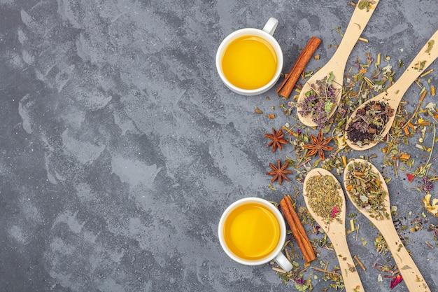 Ассортимент сухих чаев разных сортов в деревянных ложках и две чашки зеленого чая. органический травяной, зеленый и черный чай с сухими цветочными лепестками для чайной церемонии