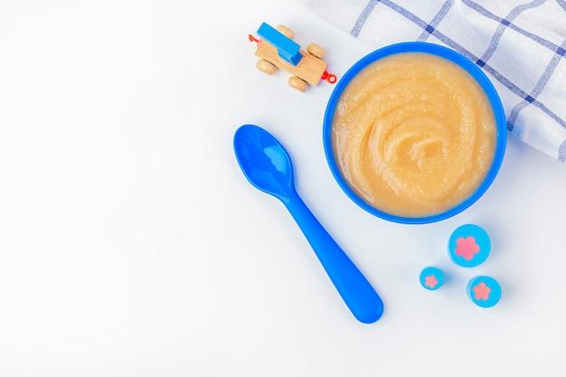 ベビーフード。新鮮な自家製アップルソース。生地にフルーツのピューレ、テーブルに子供のおもちゃが入った青いボウル。適切な栄養と健康的な食事の概念。オーガニックおよびベジタリアン料理