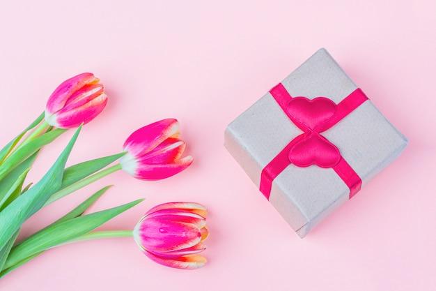 新鮮な赤いチューリップの花と白い背景のギフトボックスの花束。休日の国際女性の日、母の日、バレンタインの日、誕生日、記念日、その他のイベントでの女性への贈り物。