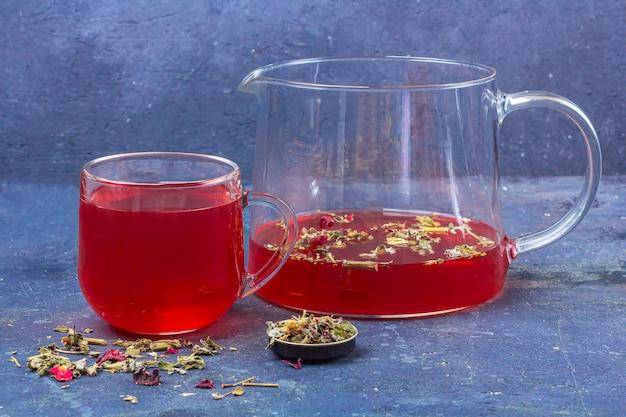 乾燥茶葉と暗い背景の花びらの間でガラスカップとティーポットの赤茶(ルイボス、ハイビスカス、カルカデ)。風邪やインフルエンザのためのハーブ、ビタミン、デトックスティー
