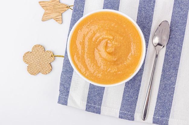 Свежее домодельное яблочное пюре в белом шаре на белой таблице. концепция правильного питания и здорового питания. органическая и вегетарианская еда. детская еда