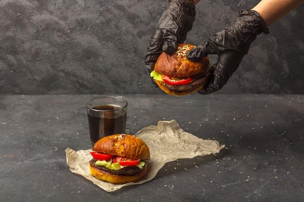 Шеф-повар в черных перчатках кладет свежеприготовленный говяжий гамбургер на гриле на пергаментную бумагу