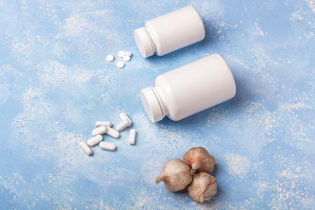 薬瓶から落ちるニンニクとハーブのサプリメント