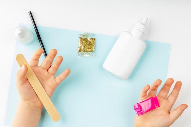 Детские руки с ингредиентами для приготовления слизи на синей бумаге