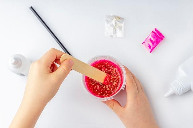 Детские руки смешивания ингредиентов для приготовления слизи на белом столе