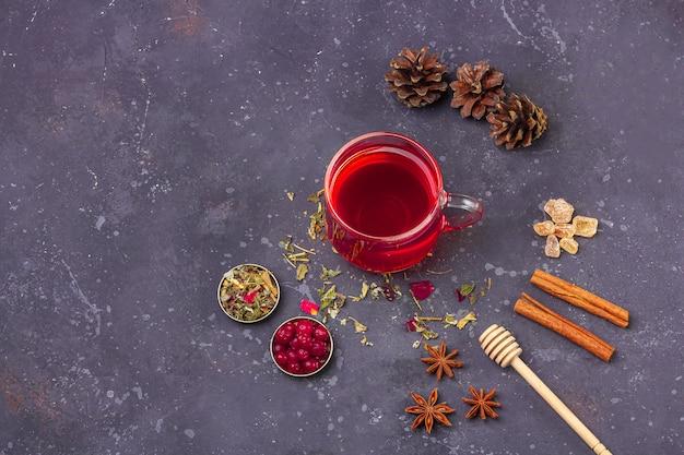 乾燥茶葉の花びらとマツ円錐形の間でガラスカップとティーポットの赤茶