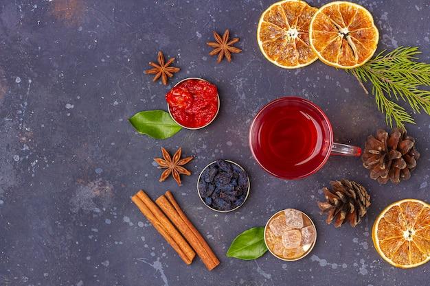 ホットスパイシーなクリスマスホームドリンク。グリューワイン、クランベリーパンチ、またはオリエンタルスタイルのごちそうのためのクランベリーとオレンジのサングリア。冬の休日の概念。クローズアップ、テキスト用のスペースをコピー、フラットレイアウト