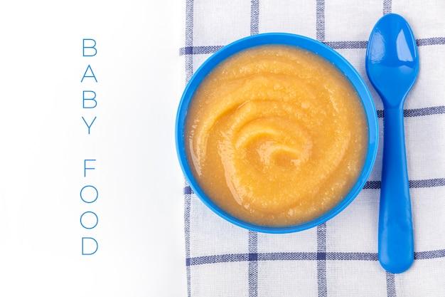 ベビーフード。新鮮な自家製アップルソース。生地にフルーツのピューレ、テーブルに子供のおもちゃが入った青いボウル。適切な栄養と健康的な食事の概念。オーガニックおよびベジタリアン料理。テキスト用のコピースペース