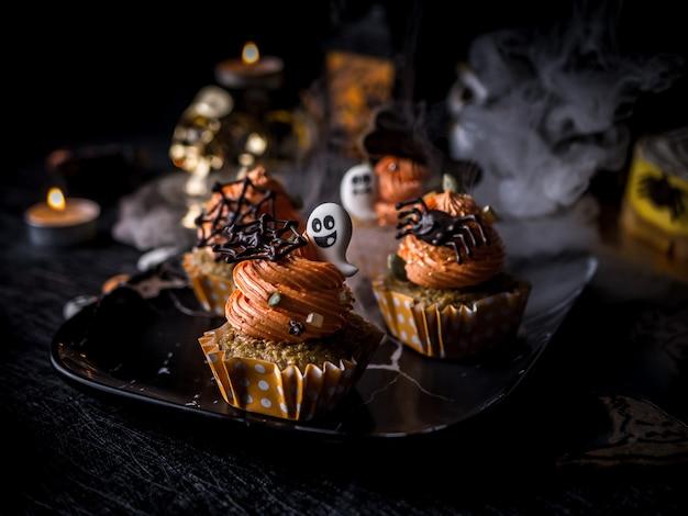 パンプキンカップケーキマフィンとクッキーの派手なハロウィーンフードパーティーテーブル。