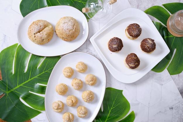 シュークリームまたはシュークリーム、またはフランスのプロフィットロールとカフェテーブルにフレッシュクリームをセット。