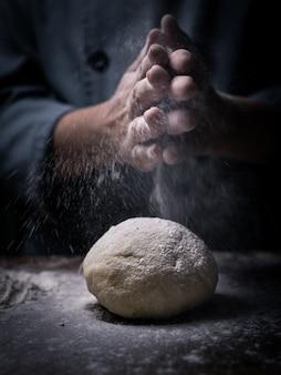 パティシエの手が台所のテーブルに生の生地の上に白い小麦粉を振りかけます。