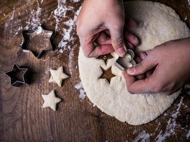 パティシエの手は台所のテーブルの上にクッキー生地をカットするためにカッティングモールドを使用します。