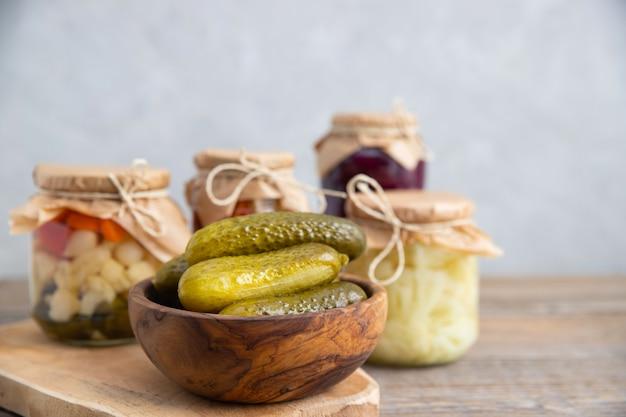 木製の丸いボウルに発酵、漬け、漬けきゅうりのクローズアップ。