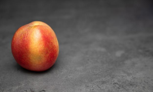 Один сочный, спелый, нектарин на сером фоне. нектарин на столе