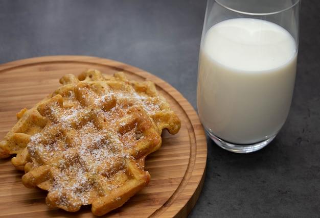 ミルクのガラスと木の板に粉砂糖とニンジンワッフル。